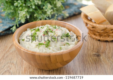 Mashed potatoes and cabbage in a wooden bowl on the table