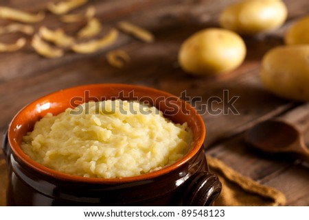 Mashed Potatoes in Terracotta Pot on Wood - stock photo