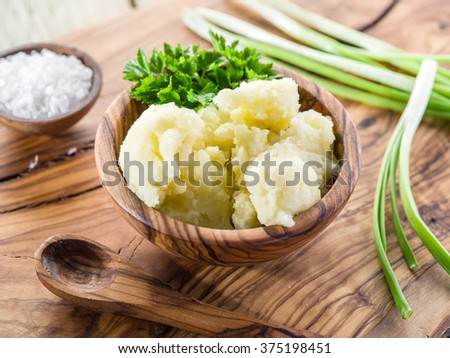 Mashed potatoes in the wooden bowl on the service tray. - stock photo