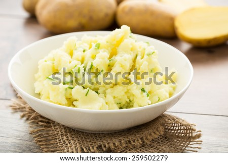 Mashed potatoes with chives served in a small bowl. - stock photo