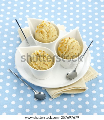 mashed potatoes with mustard in white ceramic bowls with spoons on a blue background with white polka dots - stock photo