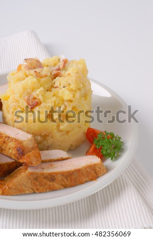mashed potatoes with sliced roasted pork meat on white plate