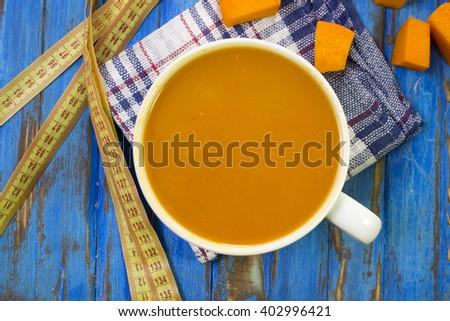 mashed pumpkin soup, pumpkin pieces, cloth, blue table, measuring tape. - stock photo