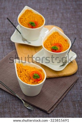 mashed pumpkin with a slice of tomato carrots in white ceramic bowls on a wooden board gray napkin - stock photo