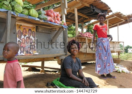 MASINDI DISTRICT, UGANDA - DECEMBER 9:Unidentified women sell vegetables on the road to Murchison Falls on December 9, 2007 near Masindi, Uganda. Selling farm products is only source money for them. - stock photo
