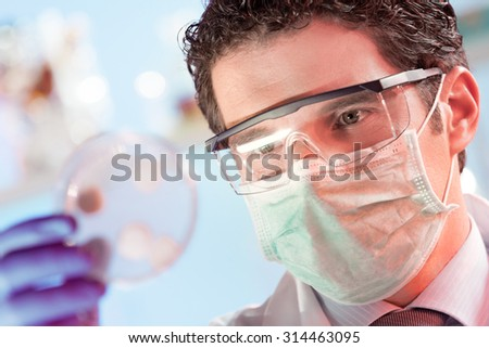 Mask and goggles protected life science researcher observing potentially infectious cells in petri dish. Focus on scientist's eye. Health care and biotechnology concept. - stock photo