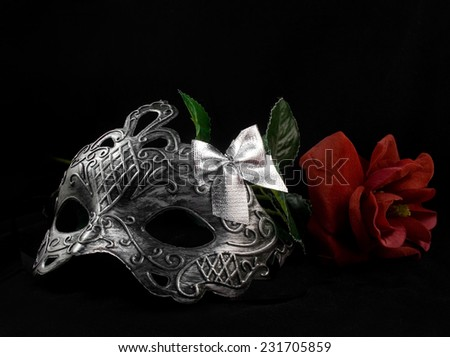 Mask and rose. Silver carnival masks laying with red rose on black fabric background.
