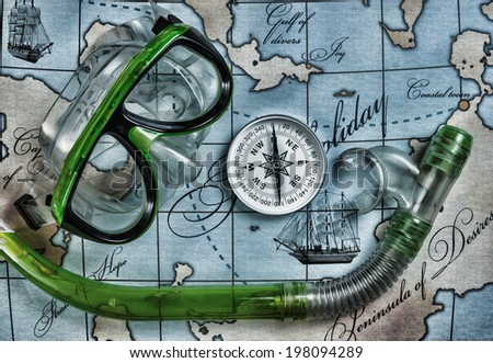 mask and snorkel diving on the map - stock photo