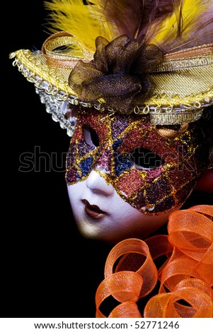 Mask on a black background, orange and feathers