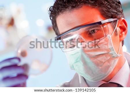 Mask protected life science professional observing the petri dish. Focus on scientist's eye. - stock photo