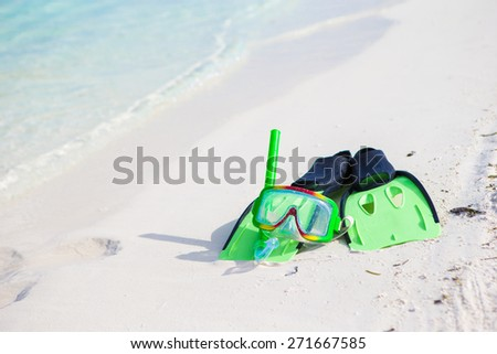 Mask, snorkel and fins for snorkeling on white sandy beach - stock photo