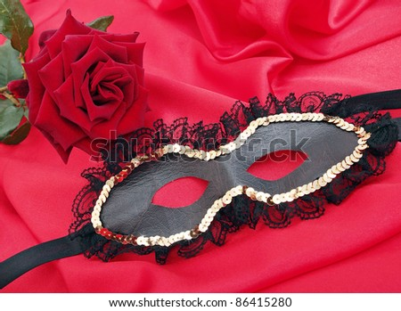 mask with the rose on the red silk - stock photo