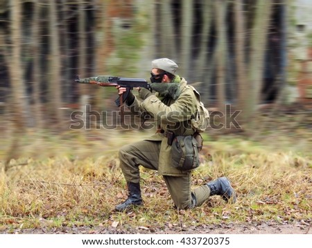 Masked airsoft player, who plays for Russian side of the army, motion blur blackground - stock photo