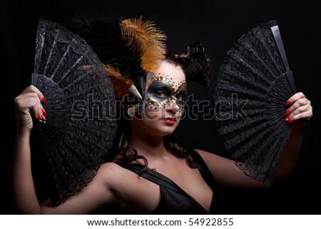Masked beautiful woman  holding fans - stock photo