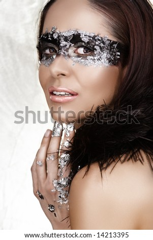 Masked beauty with silver leaf and feather boa ? visible clean skin texture