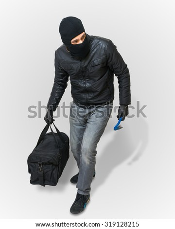 Masked burglar or thief with balaclava is creeping with black bag on white background. - stock photo