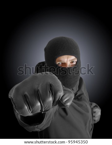 Masked criminal with clenched fist - stock photo