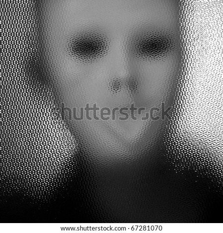 Masked distorted figure behind stained glass surface. Black and white. - stock photo