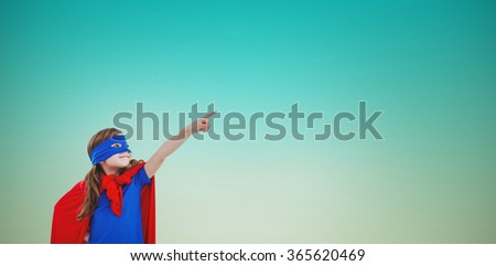 Masked girl pretending to be superhero against blue green background - stock photo