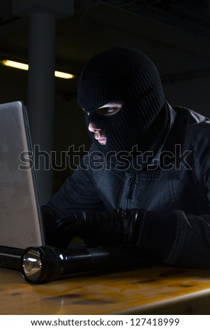 masked hacker sitting behind computer - stock photo