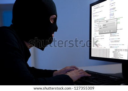 Masked hacker wearing a balaclava sitting at a desk downloading private information off a computer - stock photo