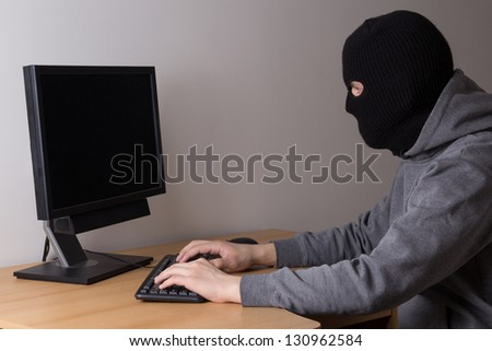 masked hacker with computer in office