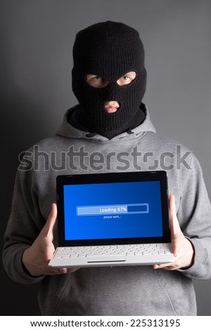 masked hacker with loading computer over grey - stock photo