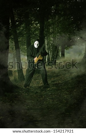 Masked mad man in the woods . Halloween and horror concept