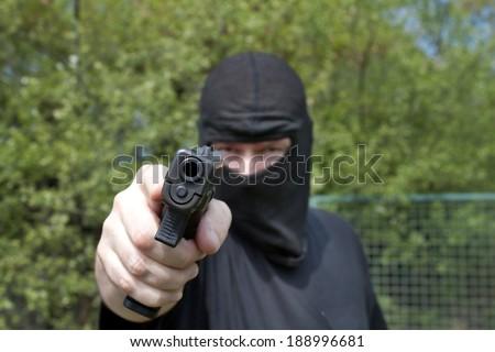 Masked man aims with gun - stock photo