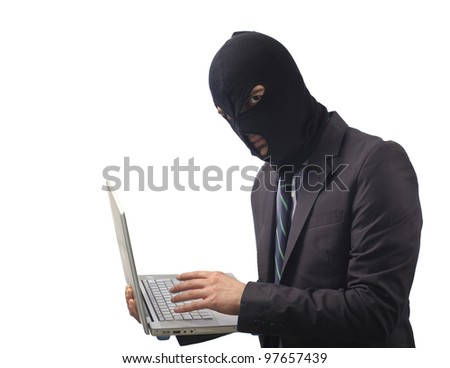 masked man hacker stealing data from a laptop - stock photo