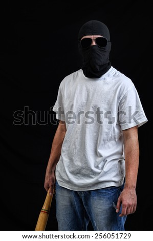 Masked man preparing to attack with bat - stock photo
