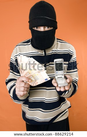 masked man with money in one hand and on the other hand a mobile phone - stock photo