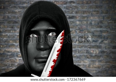Masked murderer with knife and hooded sweat shirt  - stock photo
