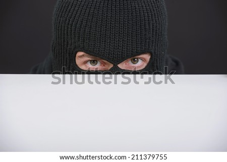 Masked robber aiming into the camera against a black background - stock photo