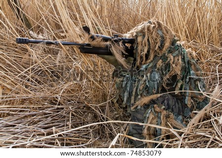 masked shooter in the reeds - stock photo