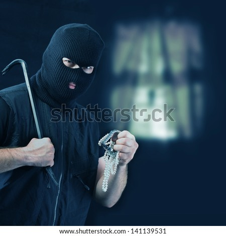 Masked thief stealing jewelry - stock photo