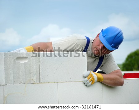 Mason aligning aerated autoclaved concrete block of constructed house wall - stock photo