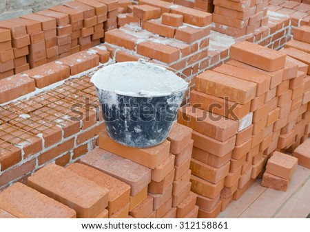 Mason bricklaying background with bucket of clay brick blocks - stock photo