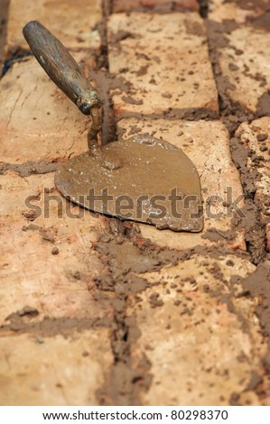 Mason bricklaying background with trowel and clay brick blocks