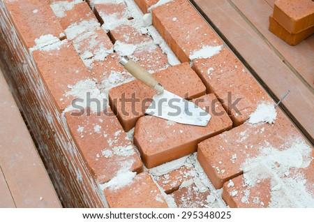 Mason bricklaying background with trowel clay brick blocks - stock photo