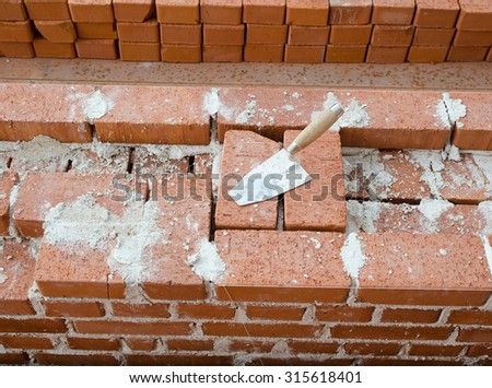 Mason bricklaying background with trowel clay brick blocks - stock photo