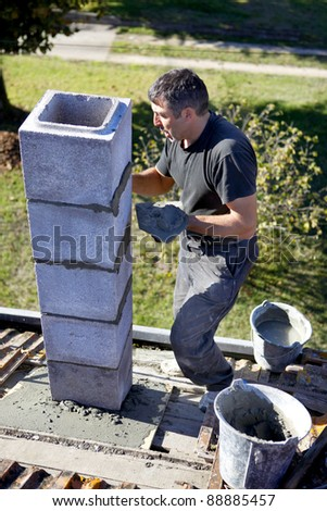 Mason building chimney - stock photo