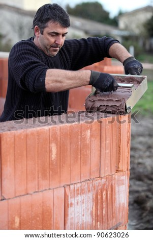 Mason carefully pouring cement - stock photo