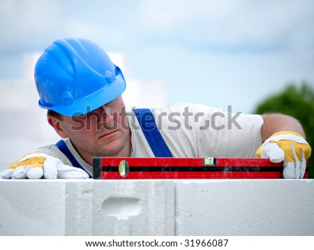 Mason checking horizontal level of house wall  layer being made from aerated autoclaved concrete blocks - stock photo