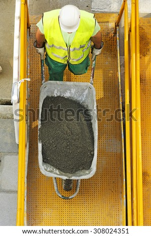 mason construction worker to load cement in the wheelbarrow  to repair road in the street city - stock photo