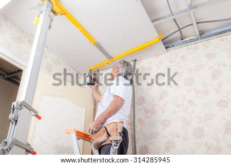 Mason drilling into a ceiling