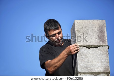 mason erecting a stone block wall - stock photo