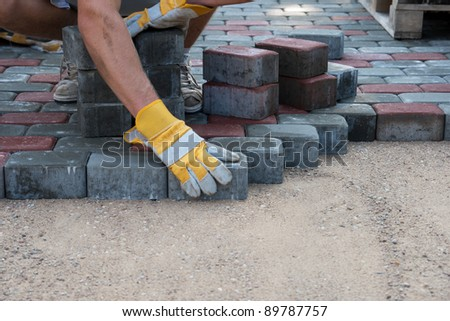 Mason is building pavement. Hands in yellow gloves lays layers of bricks. - stock photo