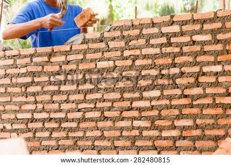 mason is masonry  brick wall : small building home construction detail - stock photo