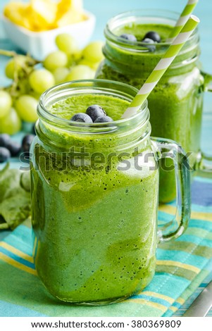Mason jar mugs filled with green spinach and kale health smoothie with green swirled straw sitting with blue striped napkin and spoons - stock photo